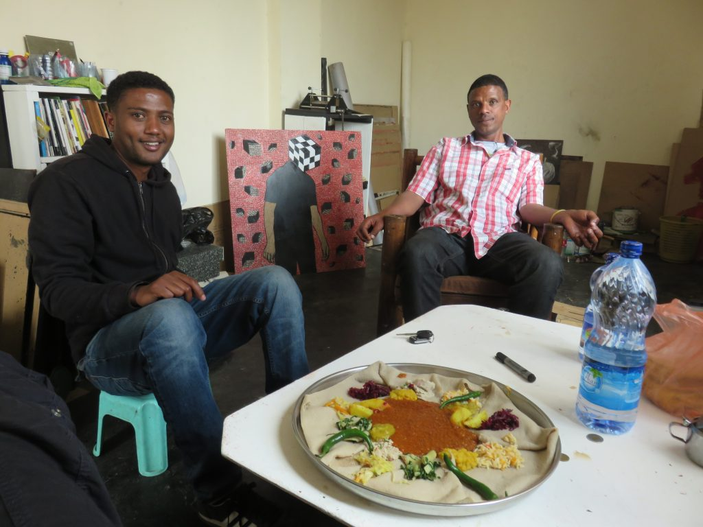 In Ephrem's studio (left) eating injera