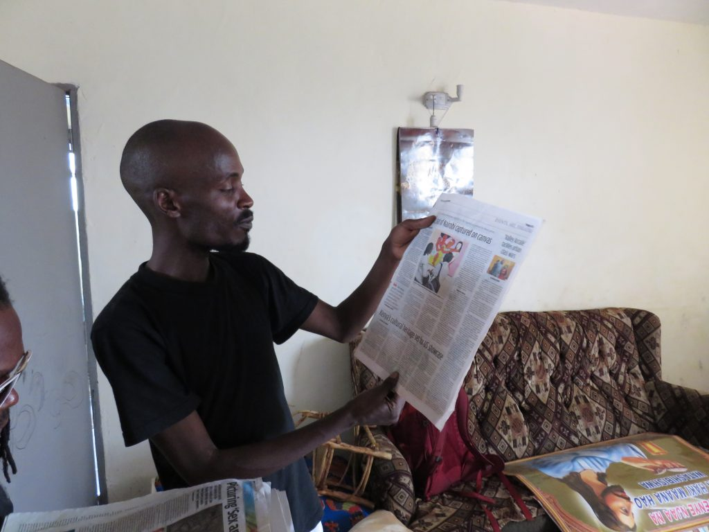 john-kamicha-showing-newspaper